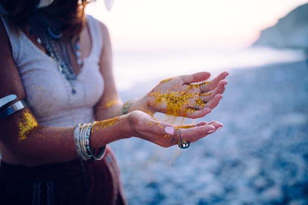 boho kvinna på strand med gyllene glitter på hennes händer - hand gold jewels bildbanksfoton och bilder