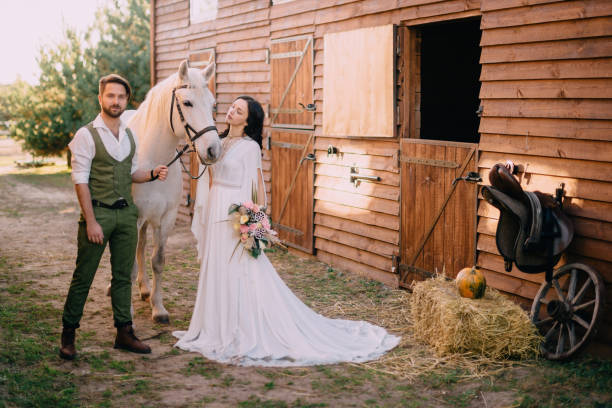 boho-style newlyweds standing near horse on ranch stock photo