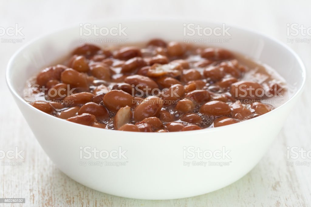 boiled beans in white dish on white wooden background stock photo