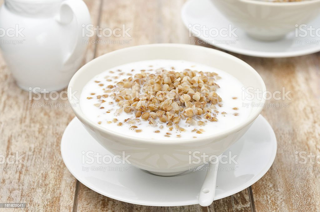 Boiled buckwheat with milk in a white bowl horizontal royalty-free stock photo