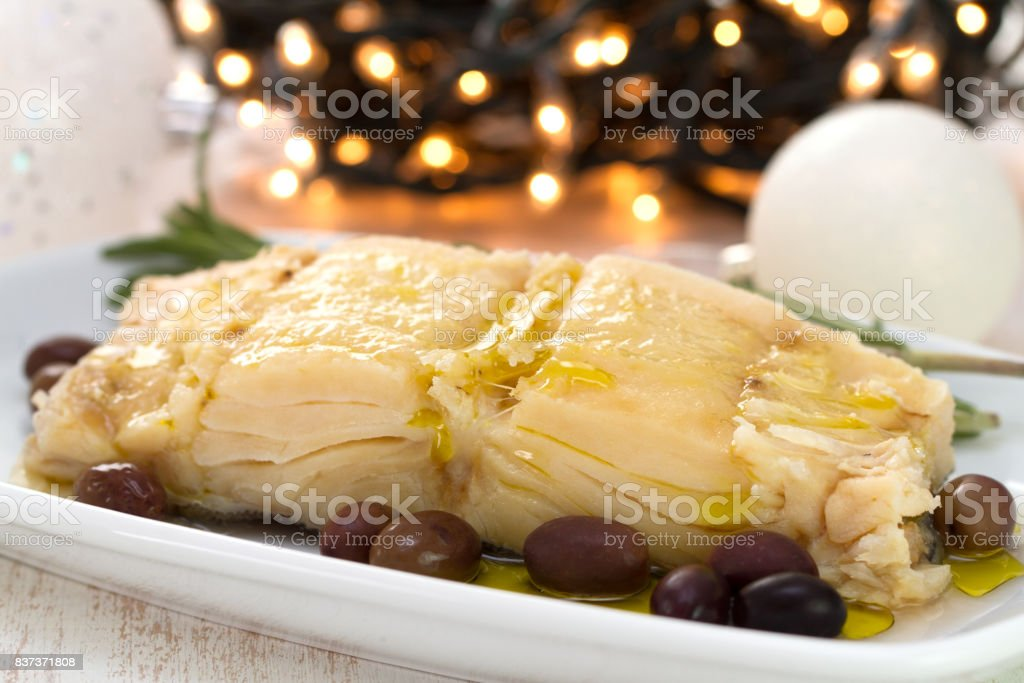 boiled cod fish with olives on white plate stock photo