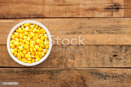Top view of white bowl full of boiled corn kernels over wooden table