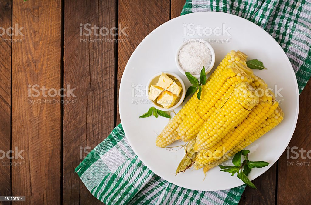 Boiled corn with salt and butter on a white plate stock photo