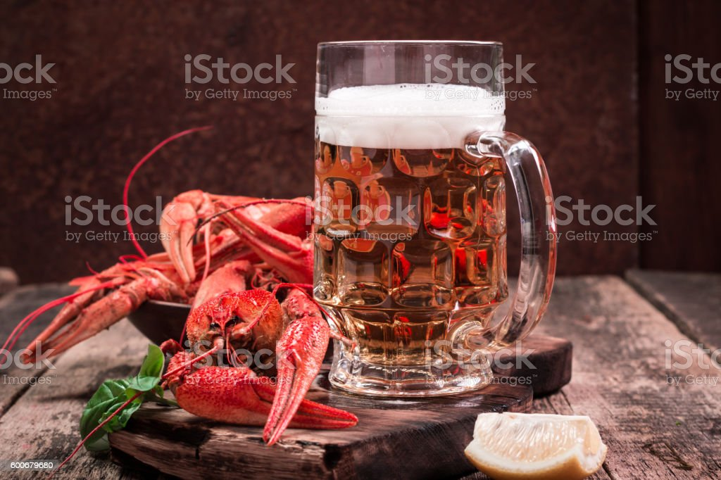 boiled crawfish and beer on a wooden background stock photo