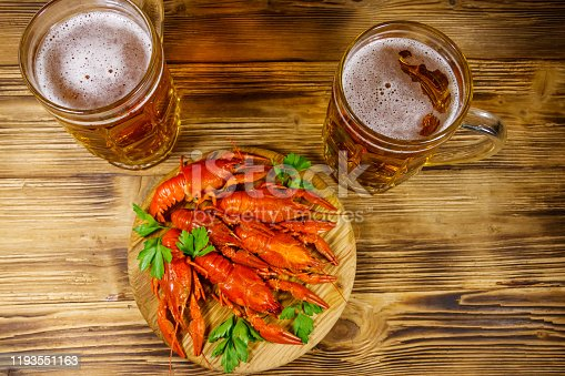 Boiled crayfish and two mugs of beer on a wooden table