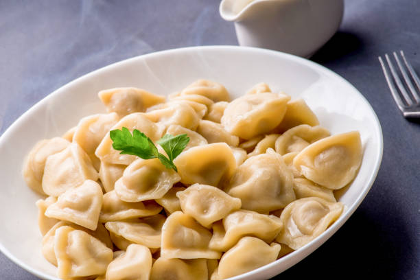 boiled dumplings with filling and sauce on the plate. Steam over a plate stock photo