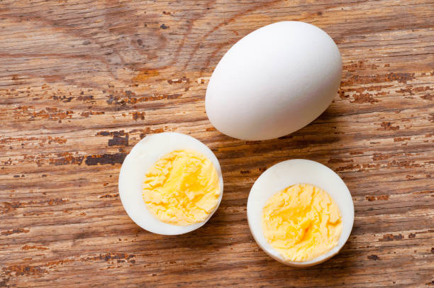 boiled egg cutout and raw egg with shell on wooden background stock photo