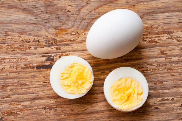gekookt ei knipsel en rauw ei met shell op houten achtergrond foto