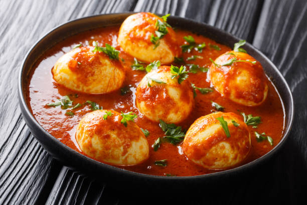 Boiled eggs cooked in spicy curry sauce close-up in a plate. horizontal Boiled eggs cooked in spicy curry sauce close-up in a plate on the table. horizontal garam masala stock pictures, royalty-free photos & images
