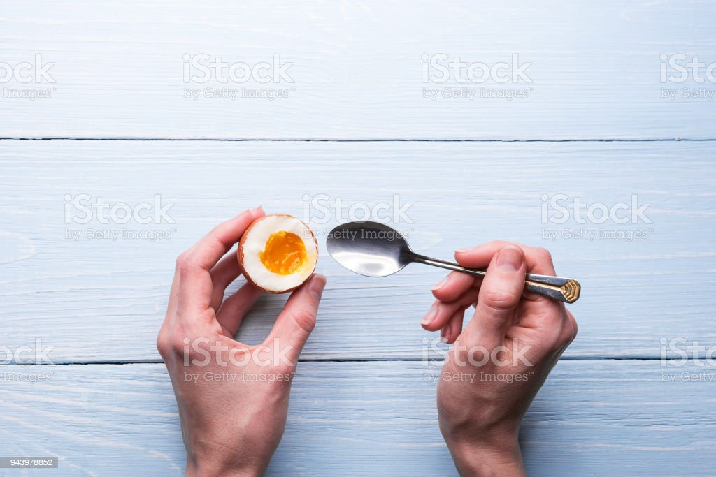 boiled eggs in hands on a wooden background stock photo