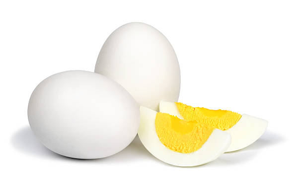 Boiled eggs on white background. Two whole unpeeled boiled eggs and two slices of eggs isolated on a white background. egg white stock pictures, royalty-free photos & images