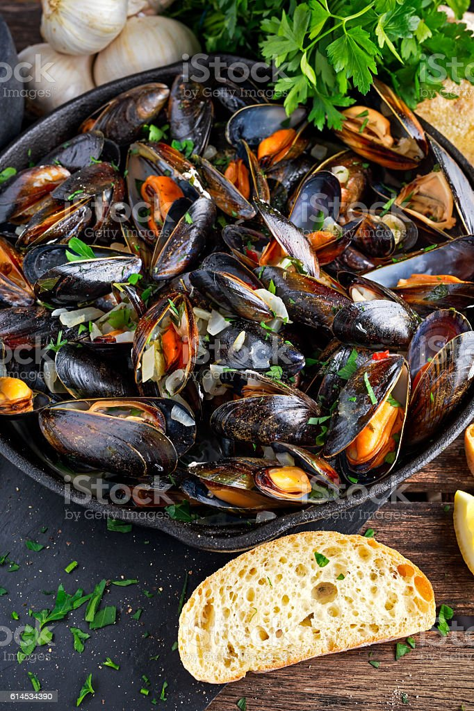 Boiled mussels in iron pan cooking dish. with herbs, butter stock photo