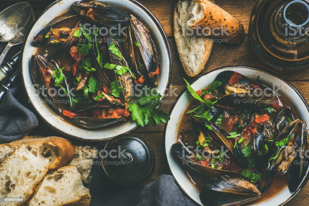 Boiled mussels in tomato sauce and beer over wooden background stock photo