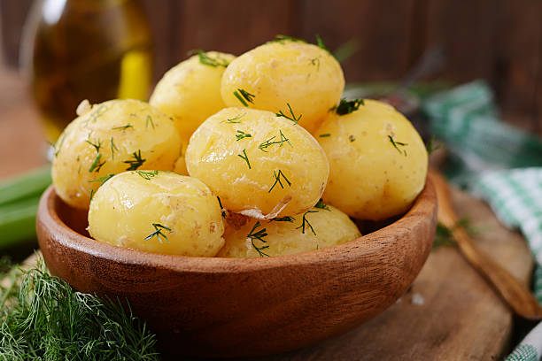 Boiled new potatoes seasoned with dill and butter stock photo