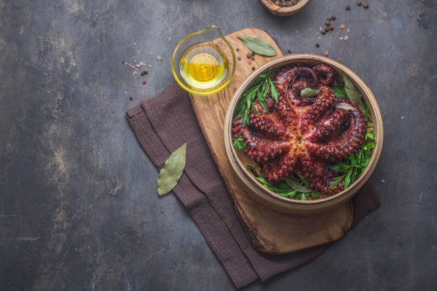 Boiled octopus with herbs and spices in wooden plate, copy spase stock photo