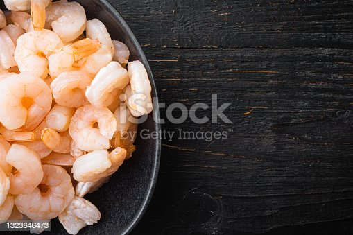 istock Boiled Peeled Shrimps, Prawns, in bowl, on black wooden table , top view flat lay, with copy space for text 1323646473