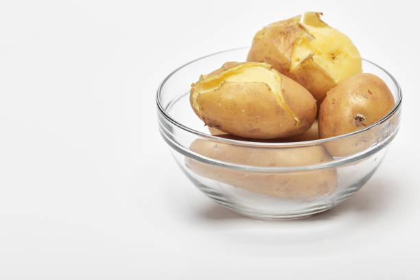 gekochte kartoffeln in einer glasschüssel auf weiß - salzkartoffel stock-fotos und bilder