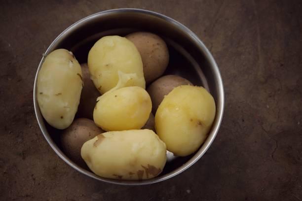 gekochte kartoffeln in einer stahlschale isoliert auf bodenboden - salzkartoffel stock-fotos und bilder