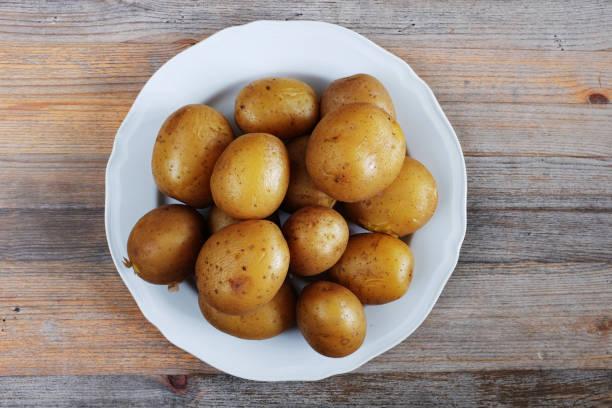 gekochte kartoffeln in ihre haut auf einem teller, mit hölzernem hintergrund - salzkartoffel stock-fotos und bilder