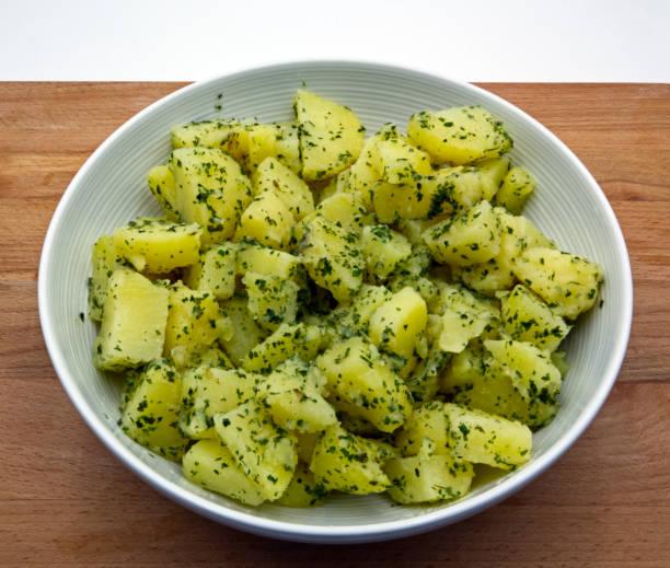 gekochte kartoffeln mit petersilie in weißer schüssel, holztisch - salzkartoffel stock-fotos und bilder