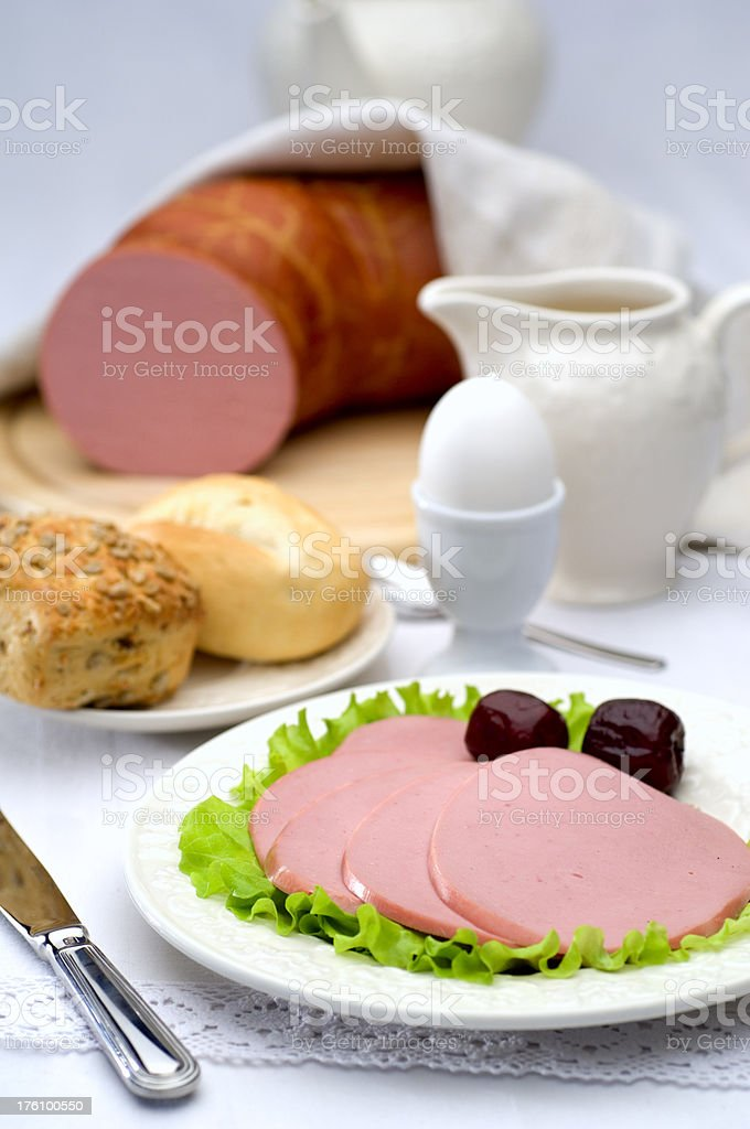Boiled sausage served with olive and egg for fine dining royalty-free stock photo