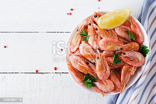 Boiled  shrimps or prawns on a white bowl on a white table. Seafood. Overhead, top view, flat lay