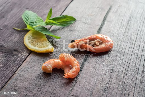 Boiled shrimps with lemon and mint on wooden table