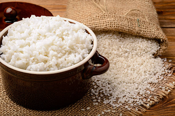 Boiled white rice in ceramic pot on wooden background. stock photo