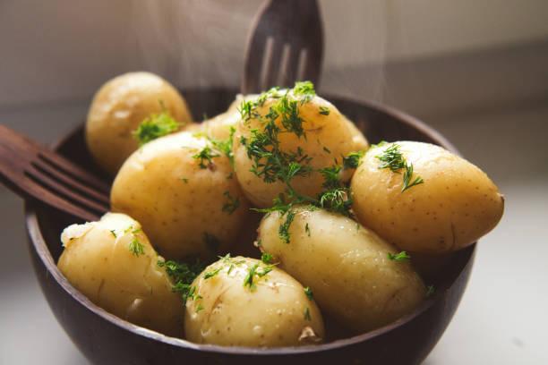 gekochte jungkartoffeln mit butter und dill in der kokosnussschale servieren - salzkartoffel stock-fotos und bilder