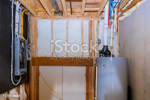 Boiler and pipes of the heating system a home framing with basement, control panel with wires wiring terminals in the electrical