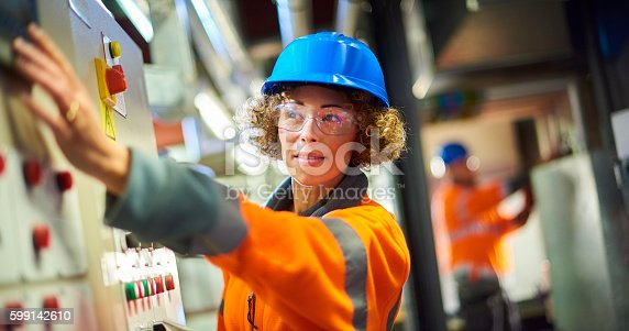 A female industrial service engineer conducts a safety check of a control panel in a boiler room. She is wearing hi vis, hard hat, safety glasses and holding a digital tablet as she conducts a safety inspection. She is reaching for one of the dials as she looks to camera.