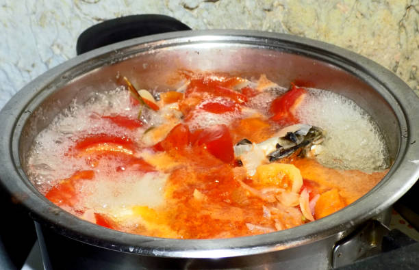 Boiling a fish soup in the metal pot stock photo