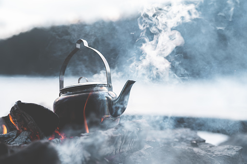Close-up of a kettle boiling coffee by a campfire. Shot in Sweden on a cold winter afternoon.