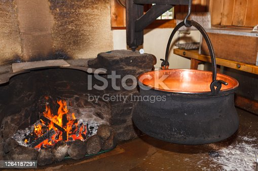 Large cauldron of boiling milk in a farmhouse for the making of cheese.