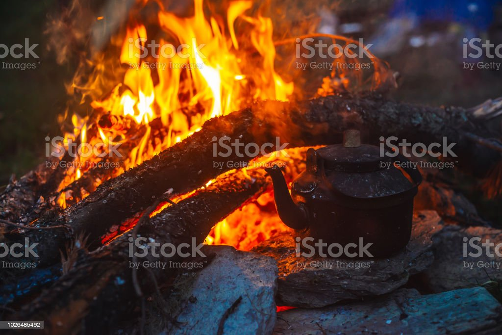 Boiling of tea in kettle on bonfire with large firewood. Tea drinking...