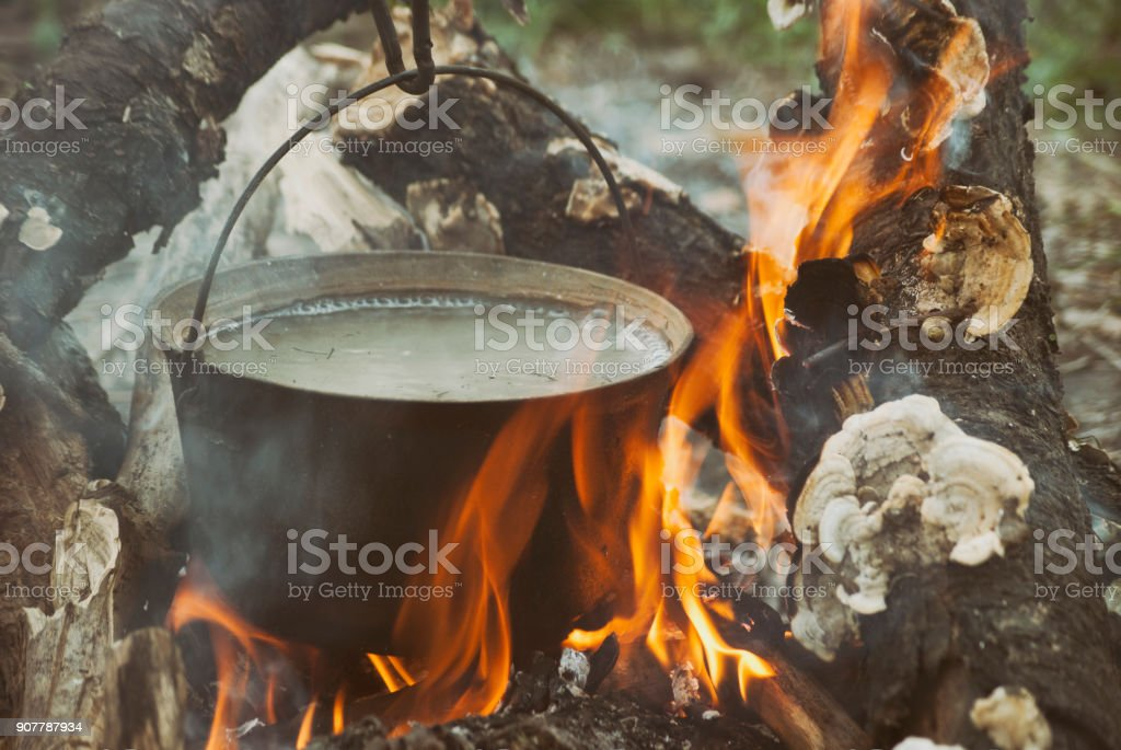 Boiling water in the bowler on the bonfire stock photo