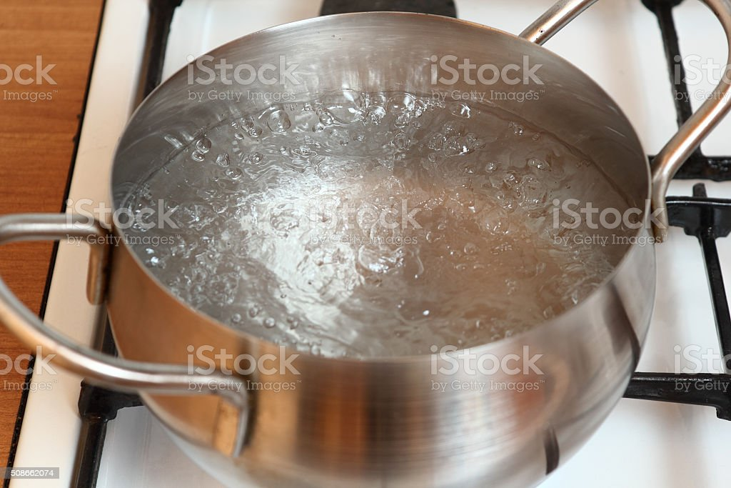 Boiling water into saucepan stock photo