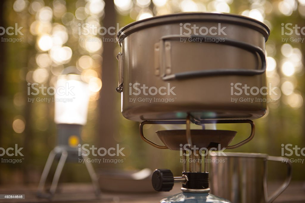 Boiling water on a small backpacking stove stock photo