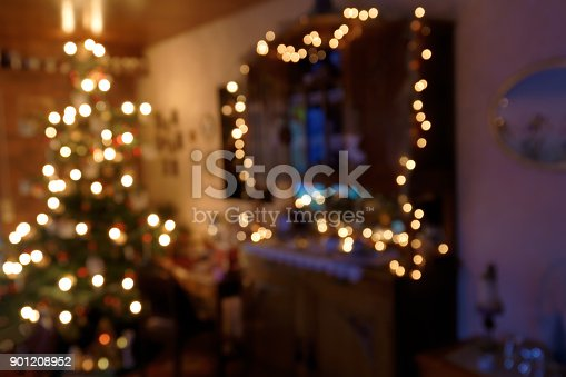 blurred atmospheric image of a family room during Christmas time, lighted by the Christmas Tree and some fairy lights around the cupboard only