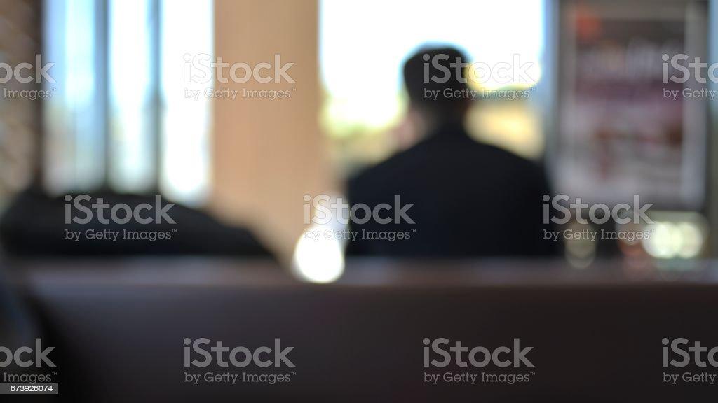 Bokeh fond - homme attend son repas au Restaurant de Fast Food photo libre de droits