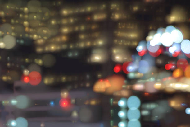 事務所の窓から、ボケ味。残業する人を置くお金の力。高層オフィスビル光夜。市の近代建築 ストックフォト