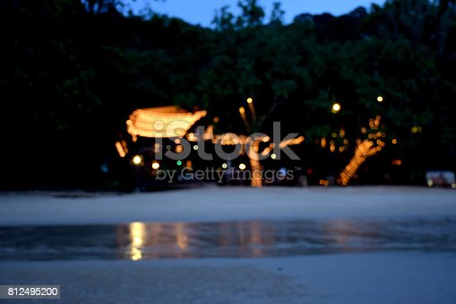 istock Bokeh light of Restaurant in front of the sea beach, image tone blurred background 812495200