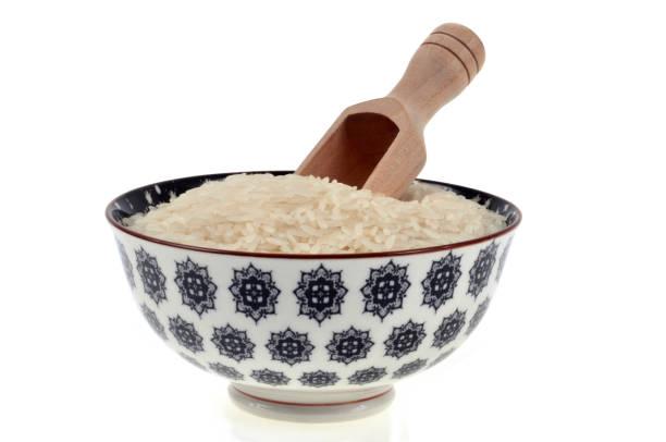 Bol de riz bol de riz sur fond blanc avec une cuillère en bois riz stock pictures, royalty-free photos & images