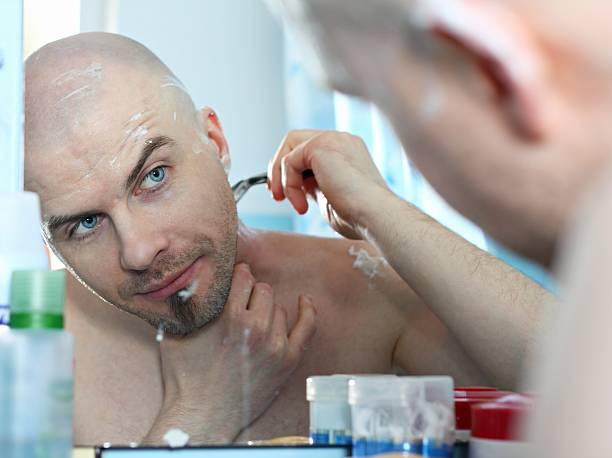 Bold man shaving stock photo