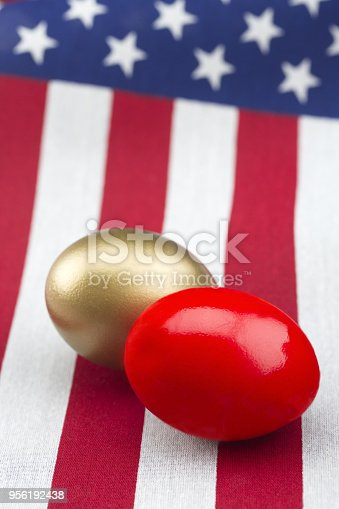red and gold nest eggs placed on American flag in vertical photograph.  Selective focus on opposing symbols of profit and loss, success and failure, reflect on financial and economic challenges.