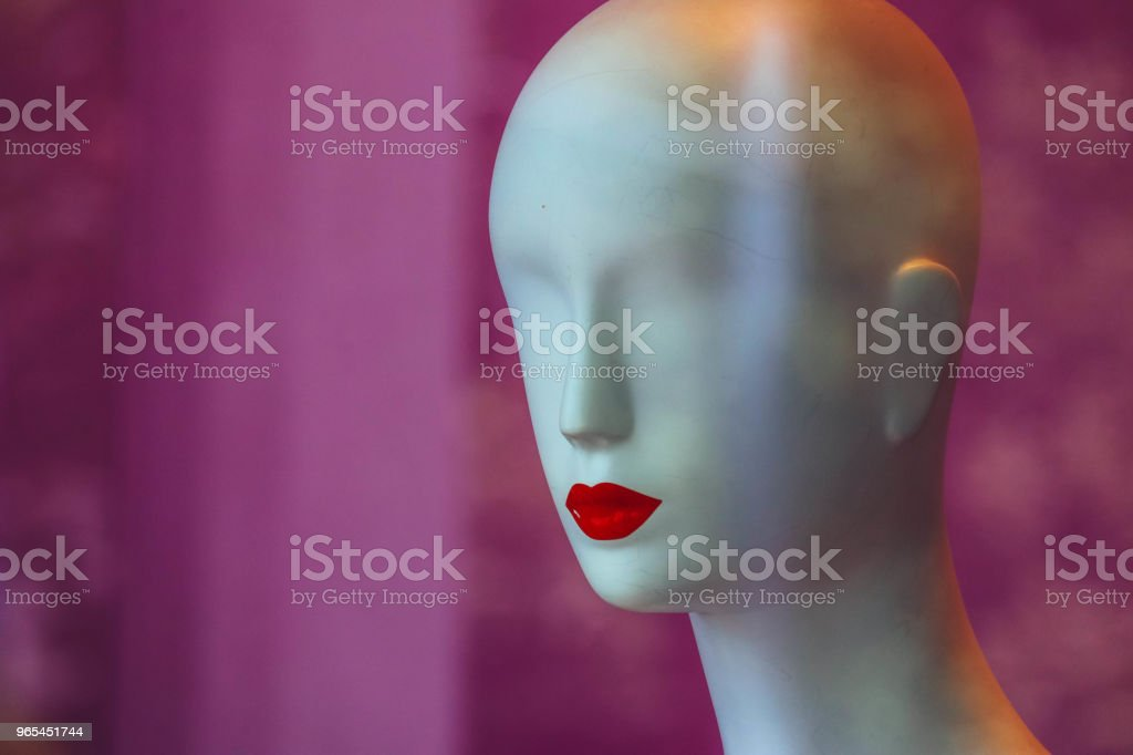 A bold white female mannequin with no eyes and red lips in a showcase of the fashion store on a black background. zbiór zdjęć royalty-free