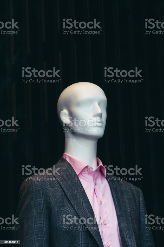 A bold white male mannequin, dressed elegant pink shirt and a jacket in a showcase of the fashion store on a black background. royalty-free stock photo