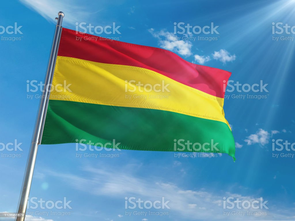 Bolivia National Flag Waving on pole against sunny blue sky background. High Definition stock photo