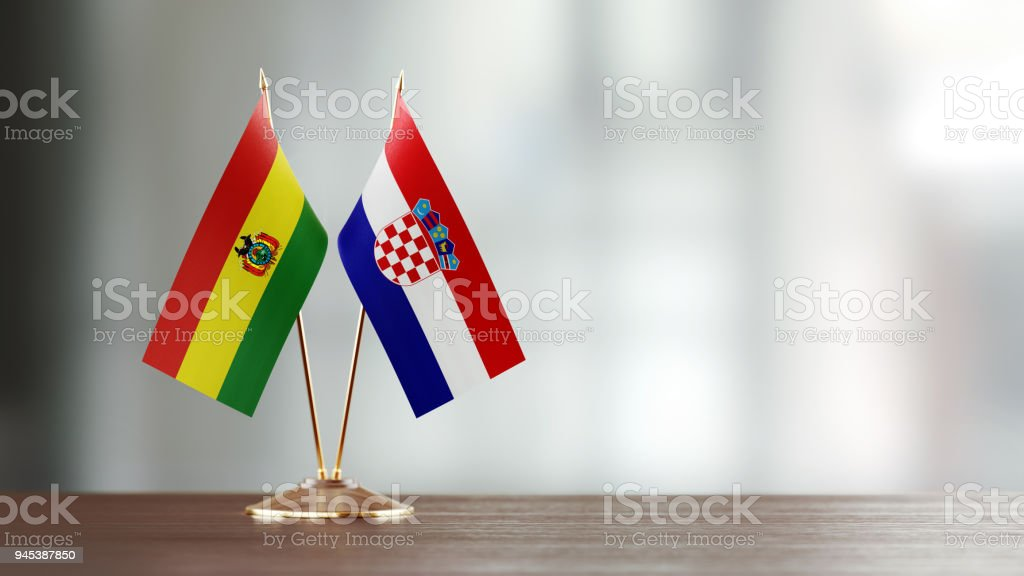 Bolivian And Croatian Flag Pair On A Desk Over Defocused Background stock photo