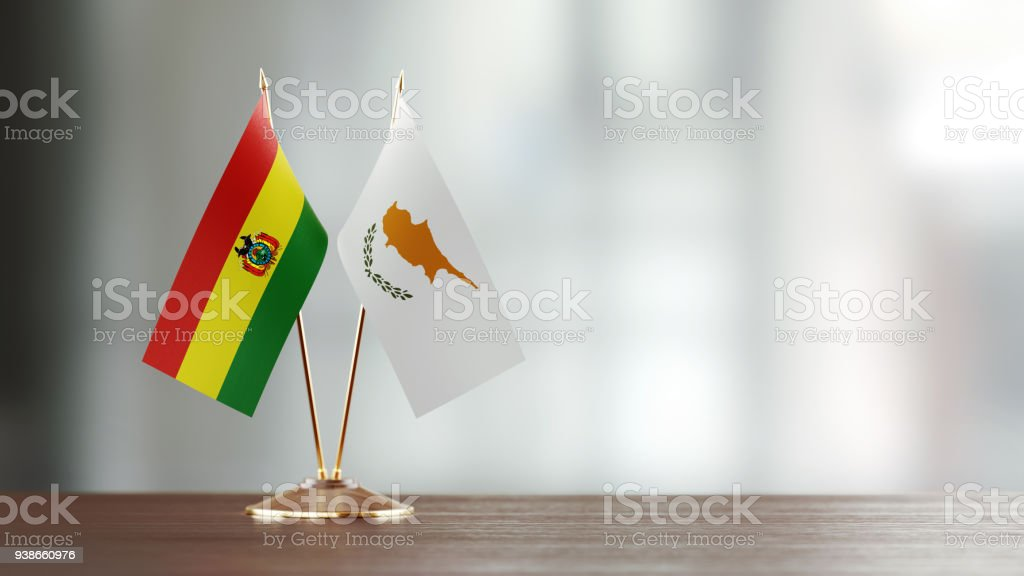 Bolivian And Cypriot Flag Pair On A Desk Over Defocused Background stock photo
